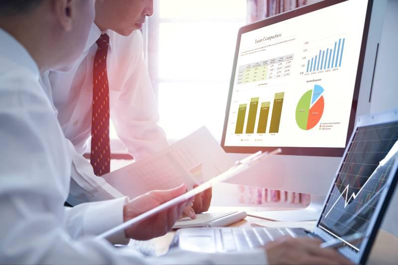 Two Asian Businessmen analysing on business loan comparison on desktop
