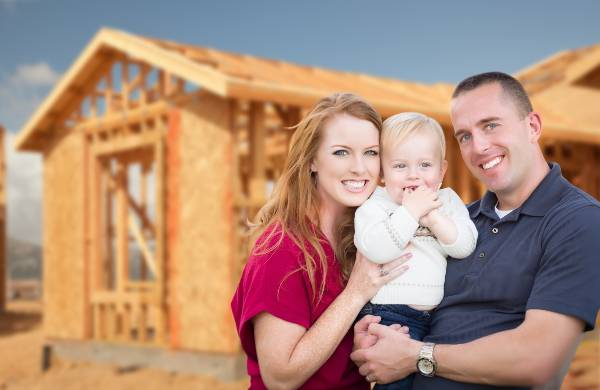 Happy Young Military Family Outside Their New Home Framing at the Construction Site